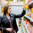 Woman buying a bottle of juice in the store — Stock Photo #73917303