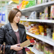 Woman checking food labelling — Stock Photo #73917385