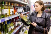Woman buying a bottle of wine in the store — Stock Photo