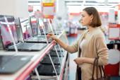 Woman choosing laptop in store — Stock Photo
