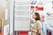 Woman buying a refrigerator in the store — Stock Photo