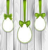 Easter three papers eggs wrapping green bows on grey wooden back — Stockvector
