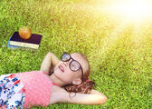 Back to school - happy girl with glasses on the grass — Stock Photo