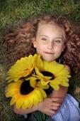 Joyful little girl lying on the grass with sunflowers — Stock Photo