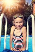 The little girl floats on a hot day at the pool — Stock Photo