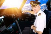 Smiling and cheerful pilot in the cockpit of an airliner — Stockfoto