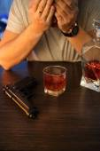 Man crying with gun and alcohol — Stock Photo