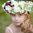 Happy little girl in a  floral wreath — Stock Photo #59597259