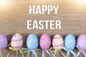 Row of colorful Easter eggs on wooden background — Stock Photo