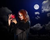 Witch with red potion on night sky background — Stock Photo