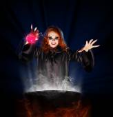 Witch with potion and cauldron on blue rays background — Stock Photo
