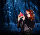 Witch with potion at night forest — Stock Photo