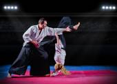 Fight between martial arts fighters at sports hall — Stock Photo