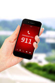 Hand holding mobile phone with emergency number 911 — Stockfoto