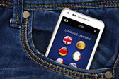 Mobile phone with language learning application in jeans pocket — Stok fotoğraf