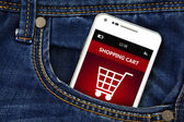 mobile phone with  shopping cart in jeans pocket — Foto Stock
