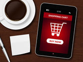 Tablet with shopping cart, cup of coffee, pen and white sheet — Stock fotografie