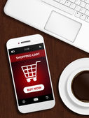 Mobile phone with shopping card page, mug of coffee and laptop k — Stock fotografie