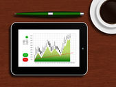 Tablet with the stock chart lying on a wooden table — Stock Photo