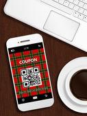 Mobile phone with christmas coupon, mug of coffee and laptop key — Stok fotoğraf