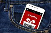 Mobile phone with christmas coupon in pocket — 图库照片