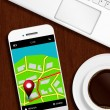 Mobile phone with gps application, laptop and coffee lying od de — Stock Photo #66624559