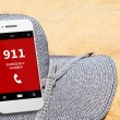 Mobile phone with emergency number 911 on the beach — Stock Photo #67066359