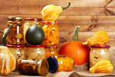 Preserved autumn vegetables on shelf in wooden wall — Stock Photo