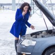Surprised woman looking under the hood of the broken machine — Stock Photo #64859625