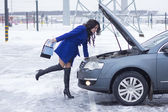 Woman carefully and look at the car engine and holding a manual car — Стоковое фото