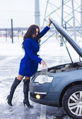 Attractive woman holding on to the hood of her car and casually looking at the engine — Stock Photo