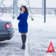 Frozen woman warms her hands on the street and waiting for a tow truck — Stock Photo #64910839