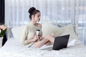 Young woman holding a coffee and read the important information from a laptop — Stock Photo