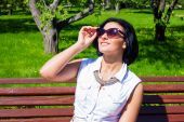 Attractive brunette in sunglasses laughing in the park on a sunny day — Stock Photo