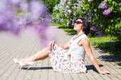 Summer mood. Woman with flowers. A woman is sitting on the pavement among the lilacs — Stock Photo