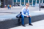 Young businessman sitting in the street near the business center and the works on the tablet — Stock Photo