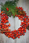 Christmas time table decoration with rose hips — Stock Photo