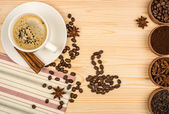 Coffee cup, anise stars, cinnamon sticks and coffee beans on woo — Stock Photo