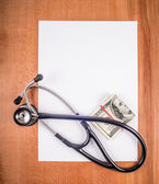Stethoscope blank sheet of paper,  and money on a wooden table. — Stock Photo