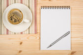 Coffee cup, spiral notebook and pen on the wooden table — Stock Photo