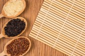 Red, white, and black rice in a wooden spoon on a wooden table — Stock Photo