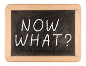 The question Now What? written by hand in white chalk on a black — Stock Photo