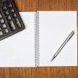 Notebook, ballpen and calculator on wooden desk — Stock Photo #70642947