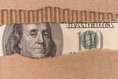 Benjamin Franklin macro peeking through torn corrugated cardboar — Stock Photo