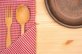 Kitchen tablecloth, fork, spoon on wooden table background — Stock Photo