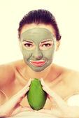 Beautiful woman with facial mask holding avocado. — Stock Photo