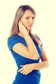 Young casual woman touching her ear. — Stock Photo