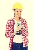 Young casual woman holding drill and wearing safety helmet. — Foto de Stock