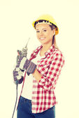 Young casual woman holding drill and wearing safety helmet. — Stock Photo