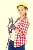 Young casual woman holding drill and wearing safety helmet. — Stock fotografie